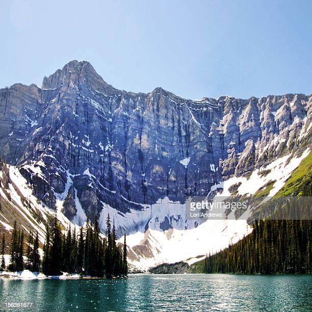 a mountain shielding a lake - kananaskis stock-fotos und bilder