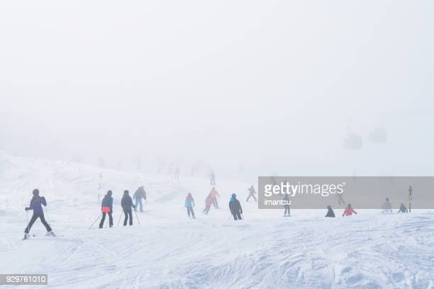 mountain skiers in a cloud of mist - ski resort stock pictures, royalty-free photos & images