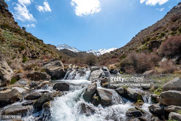 mountain stream rio valdeinfierno, hiking trail near junta de los rios, behind sierra nevada with summits mulhacen and la alcazaba, snow-covered mountains near granada, andalusia, spain - granada provincia de granada stock pictures, royalty-free photos & images