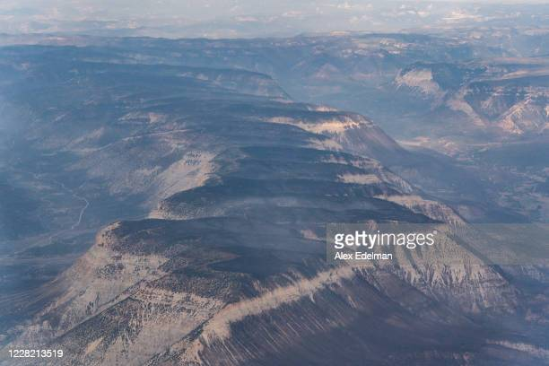 Mountain tops burned by the Pine Gulch Fire sit cleared of fire activity on August 26, 2020 in Grand Junction, Colorado. The fire, which is...