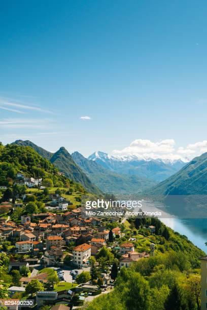 Mountain town above lake, snow capped mountains