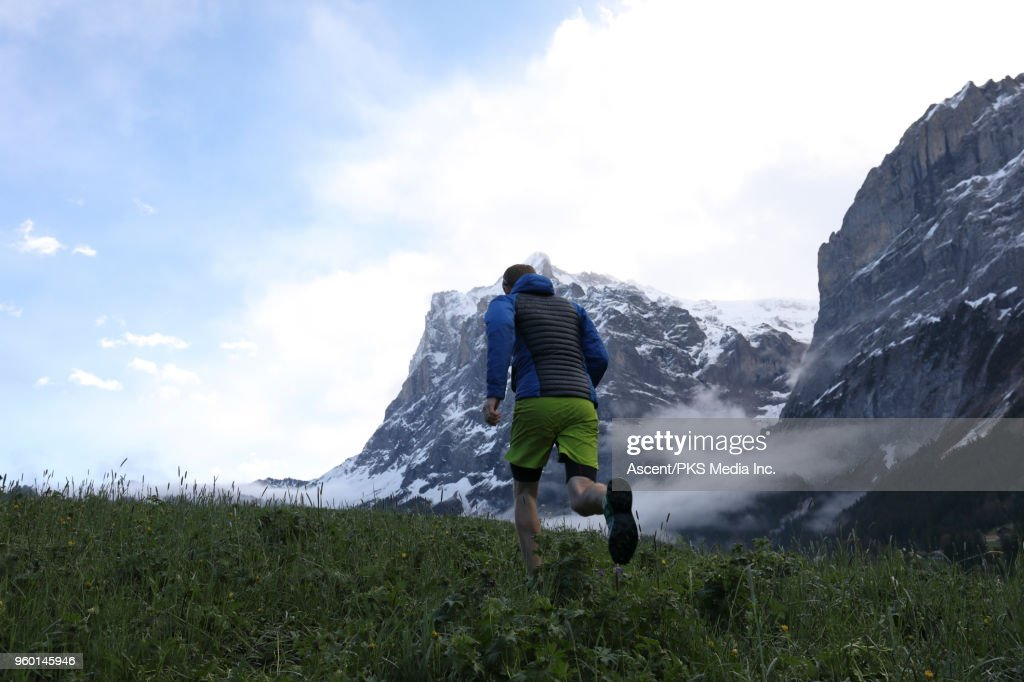 Mountain trail runner traverses meadow, below mountains : Stock-Foto