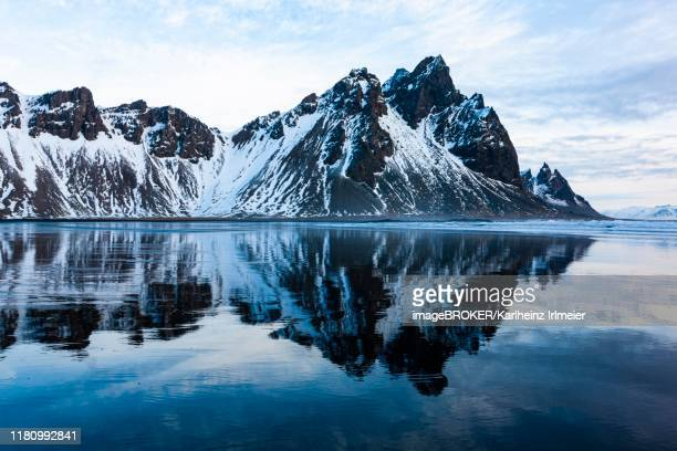 mountain vestrahorn with water reflection in the bay of hornsvik, austurland, south iceland, iceland - austurland stock-fotos und bilder
