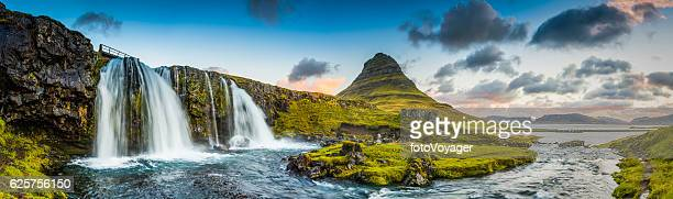mountain waterfalls below rocky peaks panorama at sunrise kirkjufell iceland - islanda foto e immagini stock