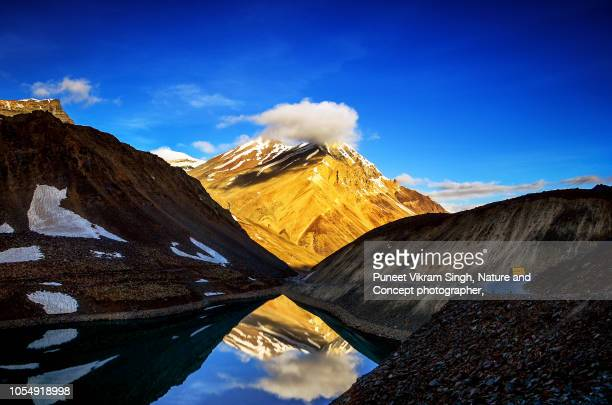 A mountain with cloud over the peak in front of Suraj Tal lake in Lahaul Valley, Himachal Pradesh