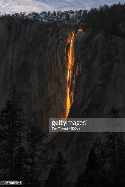 mountain with firefall - firefall stock photos and pictures
