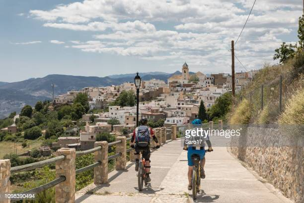 mountainbiker approaching village at andalucian sierra nevada, spain - andalucia stock pictures, royalty-free photos & images