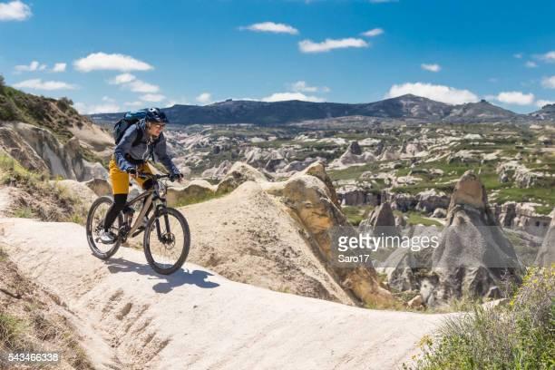 Mountainbiker balancing on white tuff formation, Cappadocia, Turkey