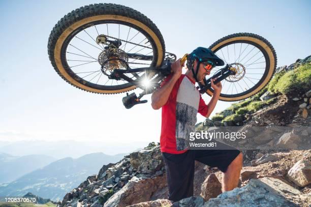 mountainbiker carrying his mountainbike - レンツァーハイデ ストックフォトと画像