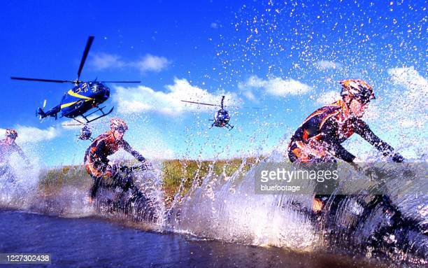 mountainbiker crossing a river with mountainbike, mountainbiking and helicopter - action movie stock pictures, royalty-free photos & images
