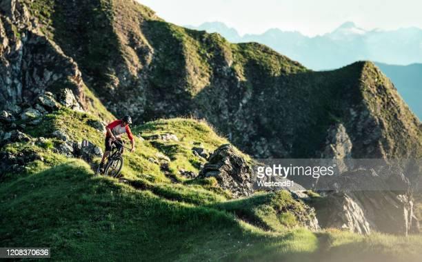 mountainbiker on a way on a ridge, grisons, switzerland - kanton graubünden stock-fotos und bilder