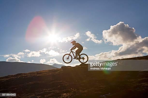 Mountainbiker on mountain bike riding a wheelie