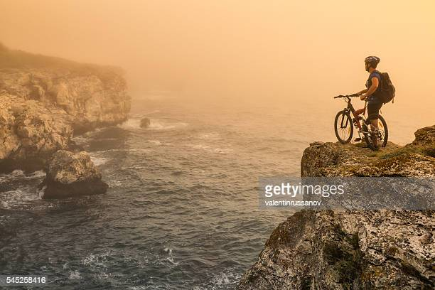 Mountainbiker standing on top of the rock