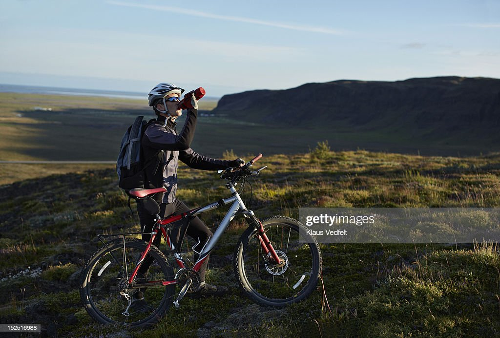 Mountainbiker taking a drinking brake on the hill : ストックフォト