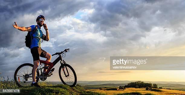 Mountainbiker aide de téléphone au sommet de la montagne