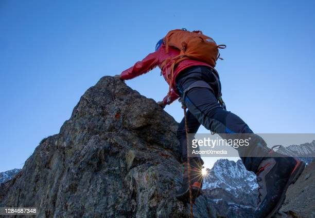 mountaineer ascends mountain ridge crest - red pants stock pictures, royalty-free photos & images