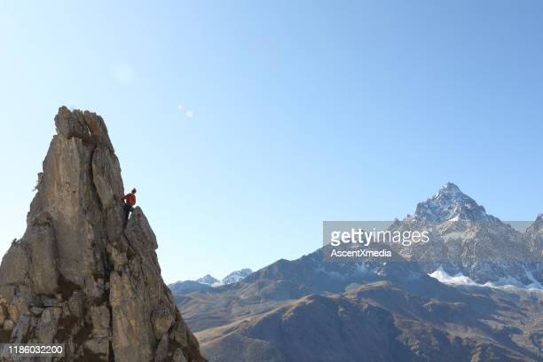 mountaineer ascends to pinnacle summit, teammate - ascent xmedia stock pictures, royalty-free photos & images