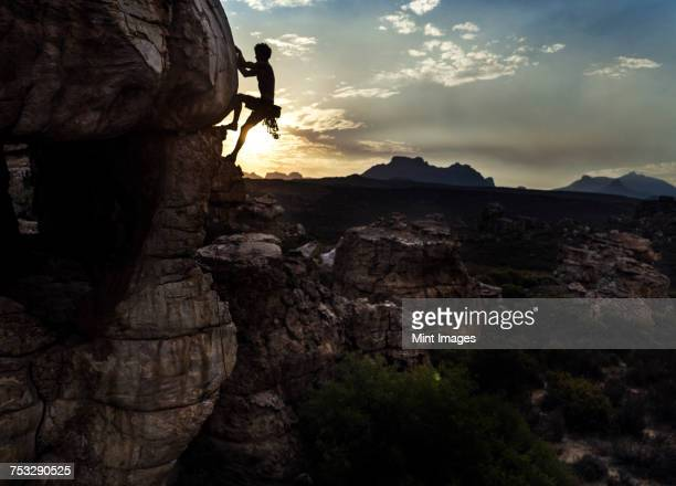 mountaineer climbing a rock formation in a mountainous landscape. - free climbing stock pictures, royalty-free photos & images