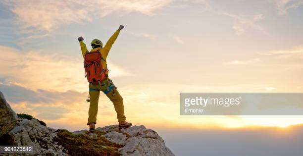 mountaineer climbing on mountain - gold jacket stock pictures, royalty-free photos & images