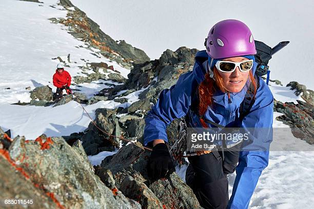 Mountaineer climbing up snow covered mountain, Saas Fee, Switzerland