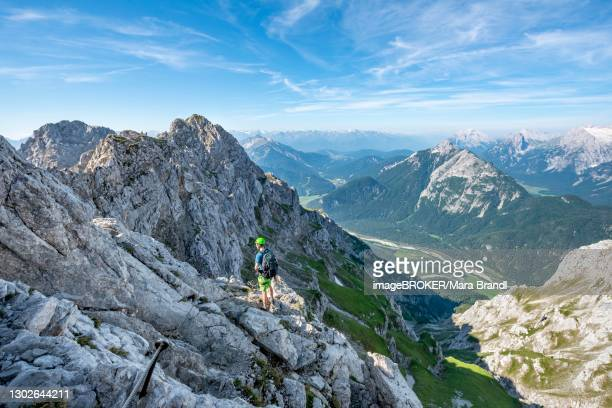 mountaineer climbs on a secured fixed rope route, mittenwalder hoehenweg, view into the isar valley near mittenwald, karwendel mountains, mittenwald, bavaria, germany - oberbayern stock-fotos und bilder