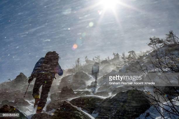 Mountaineer climbs through snowy landscape