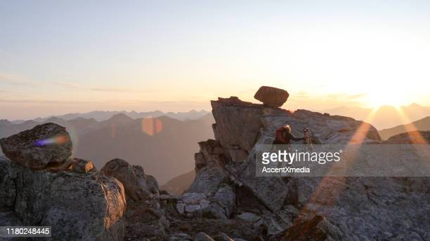 mountaineer crosses summit ridge at sunrise - ascent xmedia stock pictures, royalty-free photos & images