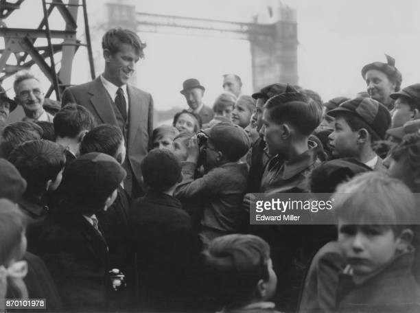 Mountaineer Edmund Hillary is greeted by young fans in the Pool of London after his return from Antarctica on the vessel 'Theron' 23rd March 1956