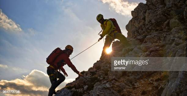 mountaineer helping his friend - climbing stock pictures, royalty-free photos & images