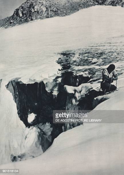 A mountaineer helps a climbing partner to cross a crevasse photo by S Orlando from L'illustrazione Italiana year LX n 49 December 3 1933