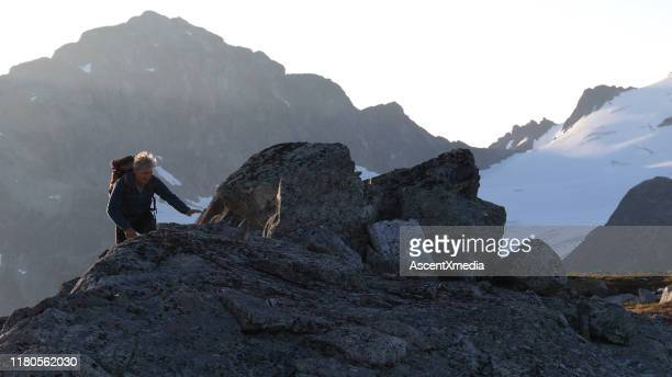 mountaineer hikes up to rocky summit at sunrise - ascent xmedia stock pictures, royalty-free photos & images