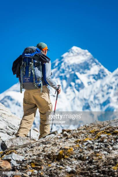 Mountaineer hiking mountain pass below Mt Everest peak Himalayas Nepal