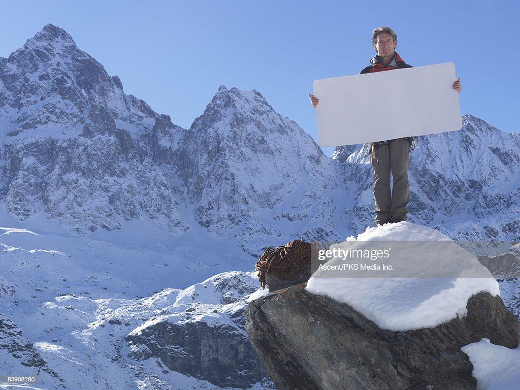 Mountaineer holding blank card on mountain summit : Stock Photo