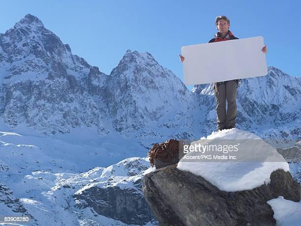 Mountaineer holding blank card on mountain summit