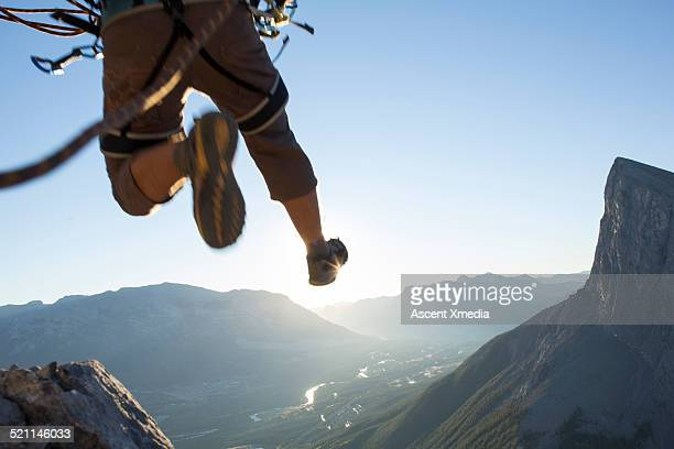 mountaineer in mid air leap above mountains - leap of faith stock photos and pictures