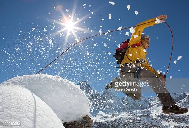 mountaineer in  mid-air jump from snowy summit - leap of faith stock photos and pictures