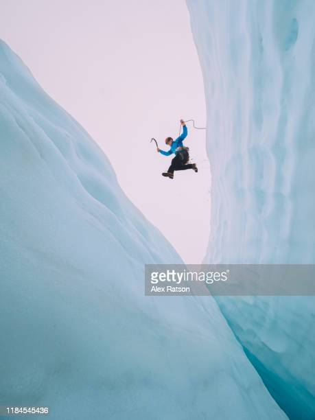 mountaineer jumps over large crevasse - risk stock pictures, royalty-free photos & images