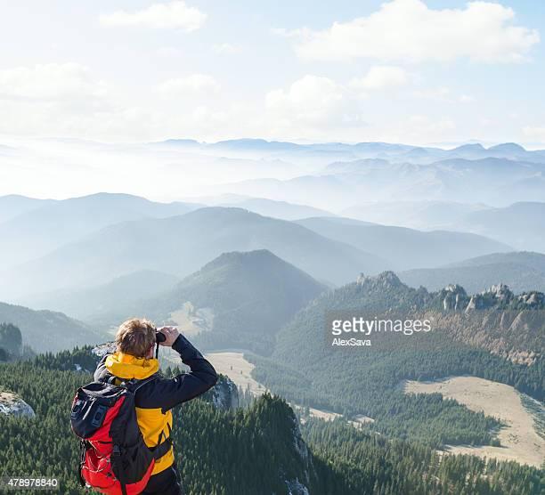 Mountaineer looking over the hills through  binoculars