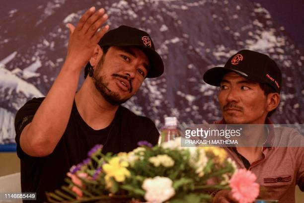 Mountaineer Nirmal Purja gestures as he speaks and Nepali mountaineer Mingma David Sherpa looks on during a press conference in Kathmandu on May 28...