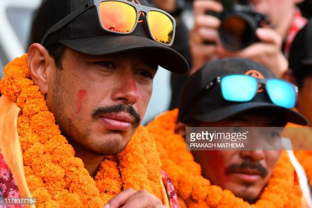Mountaineer Nirmal Purja looks on next to teammate Mingma David Sherpa after arriving at Tribhuvan airport in Nepal's capital Kathmandu on October 30...