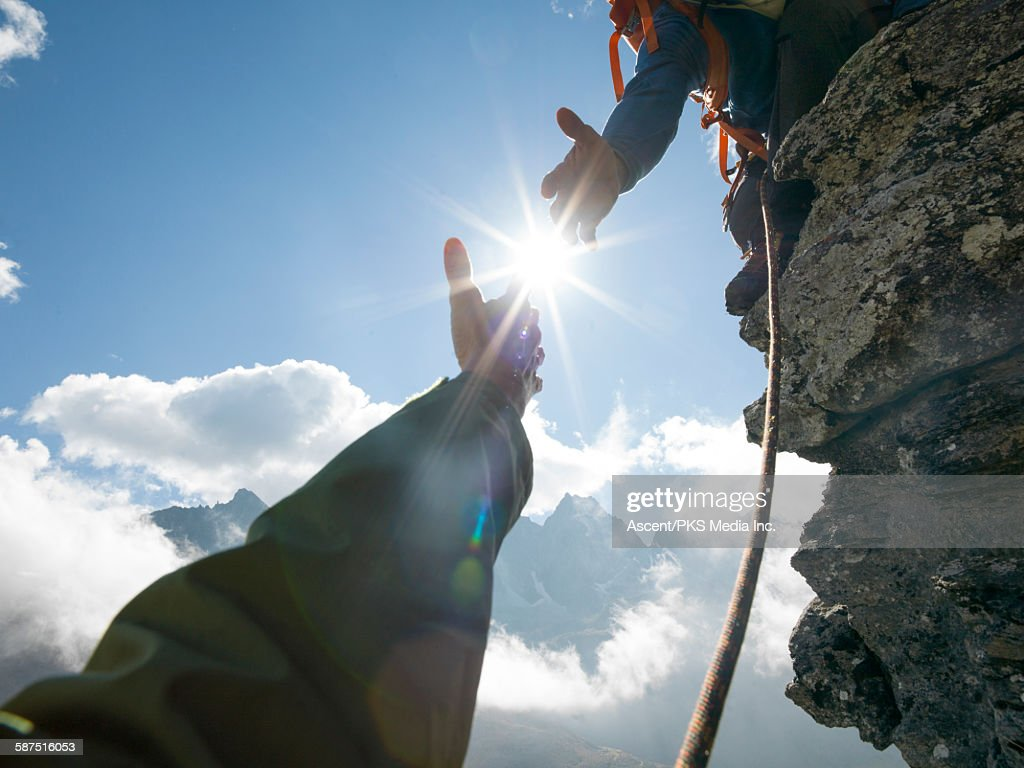 Mountaineer offers helping hand to teammate, mtns : Stock Photo