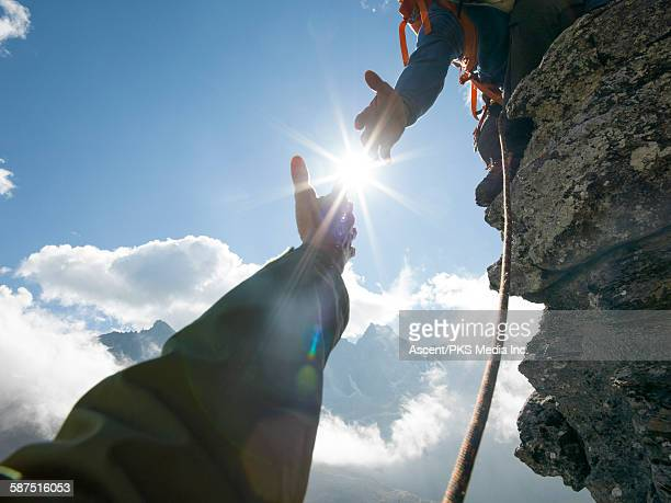 mountaineer offers helping hand to teammate, mtns - helping hand stock pictures, royalty-free photos & images