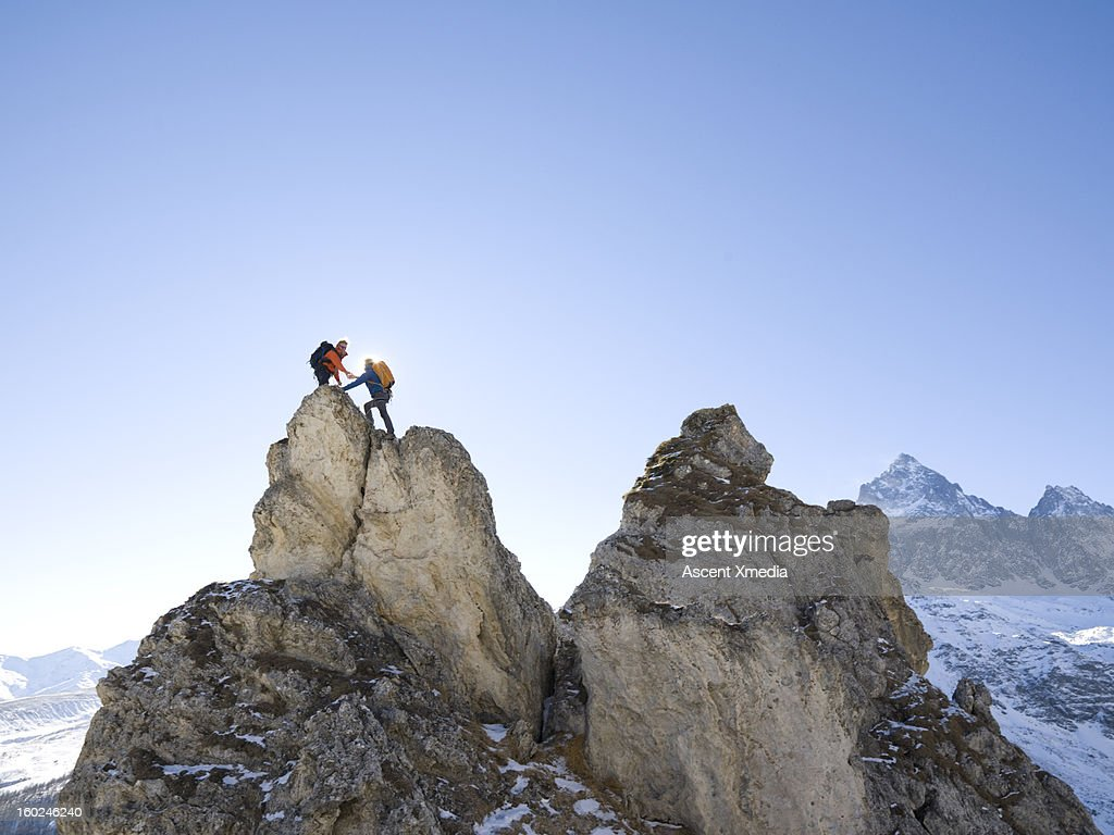 Mountaineer offers helping hand to teammate,summit : Stock Photo