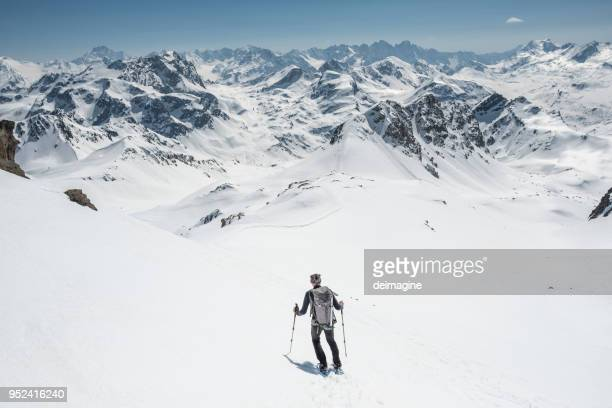 mountaineer on a snow capped majestic valley - wilderness stock photos and pictures