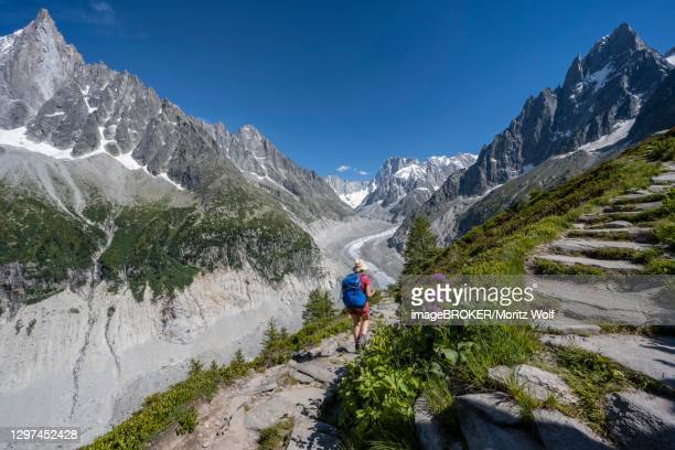 mountaineer on hiking trail, grand balcon nord, glacier tongue mer de glace, behind grandes jorasses, mont blanc massif, chamonix, france - chamonix stock pictures, royalty-free photos & images