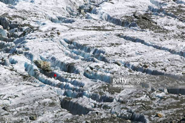 a mountaineer on the argentiere glacier melting like most alpine glaciers it is retreating rapidly due to global warming chamonix, france. - retreating ストックフォトと画像