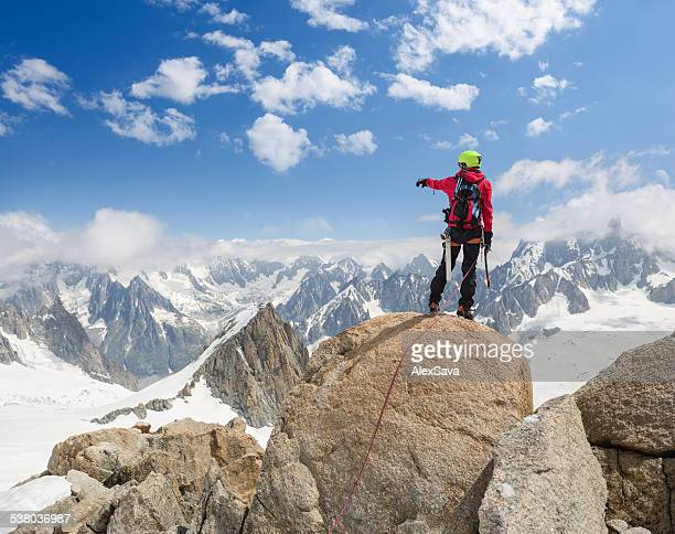 Mountaineer on top of the mountain pointing towards the Alps
