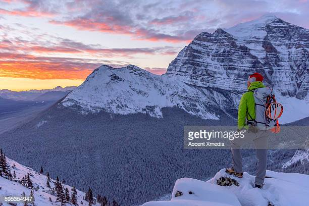 Mountaineer pauses on snowy ridge to watch sunrise