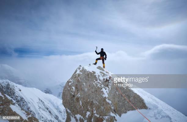 Bergbeklimmer brengt op de rots aan de rand van de wereld, op Denali.
