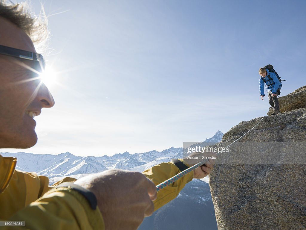 Mountaineer pulls rope tight to teammate, mtns : Stock Photo